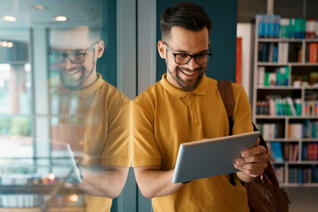 Young happy college man using digital tablet at the university - Stock Photo