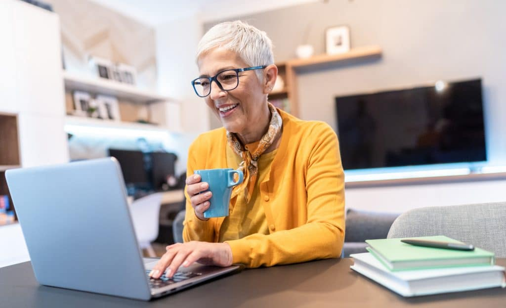 Senior woman working at home using lap top in the living room
