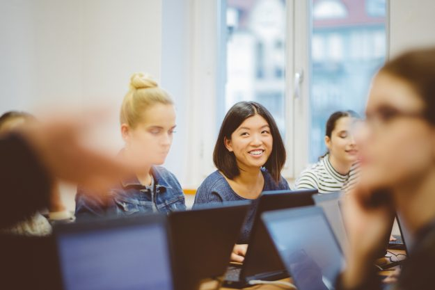 Female students learning computer programming. Focus on asian woman smiling and looking at instructor.